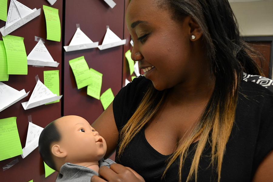 Sophomore Cynthia Karanja cuddles an electronic baby in her Childhood Development class.