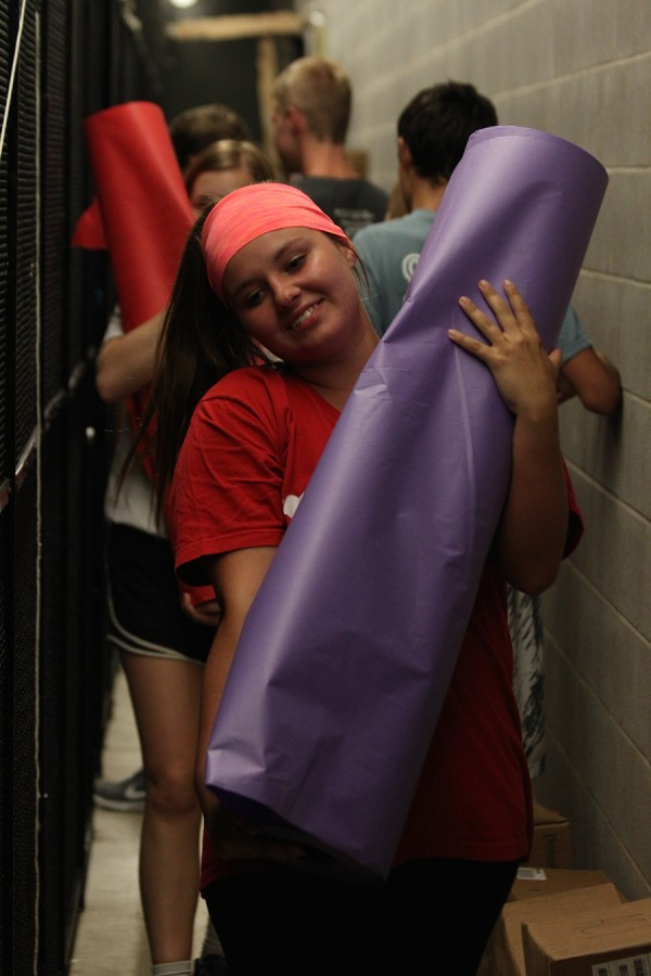 Senior StuGo representative Claire Albright carries a roll of paper to decorate during Homecoming spirit week.