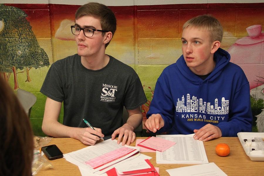 Senior Peter Hartman and sophomore Ben Murdock help people order carnations and serenades during lunch.