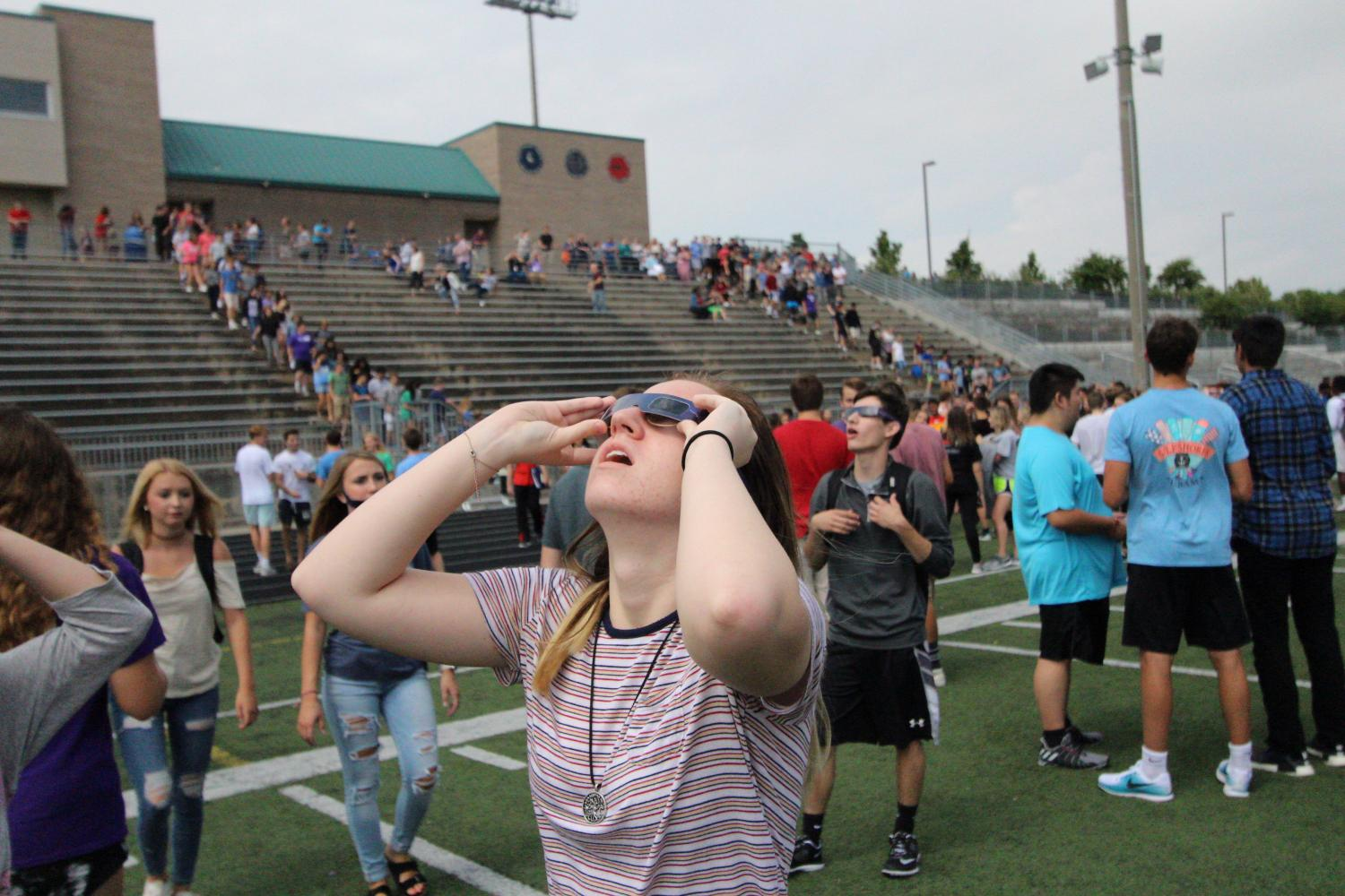 Careful to keep her protective lenses on her eyes, senior Shelby Voss glances at the sky.