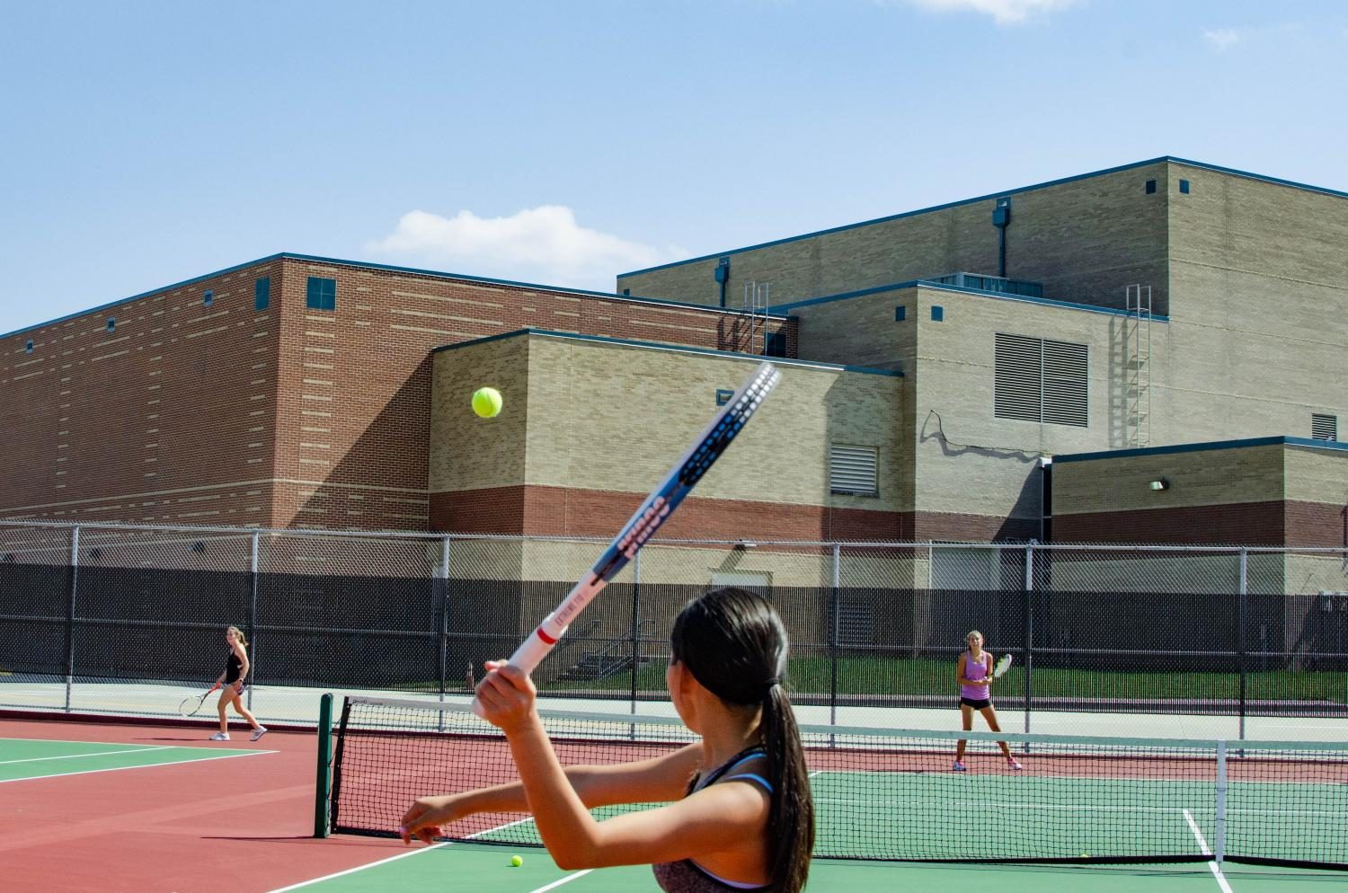 Senior Annie Zhang playing doubles at varsity tennis practice.