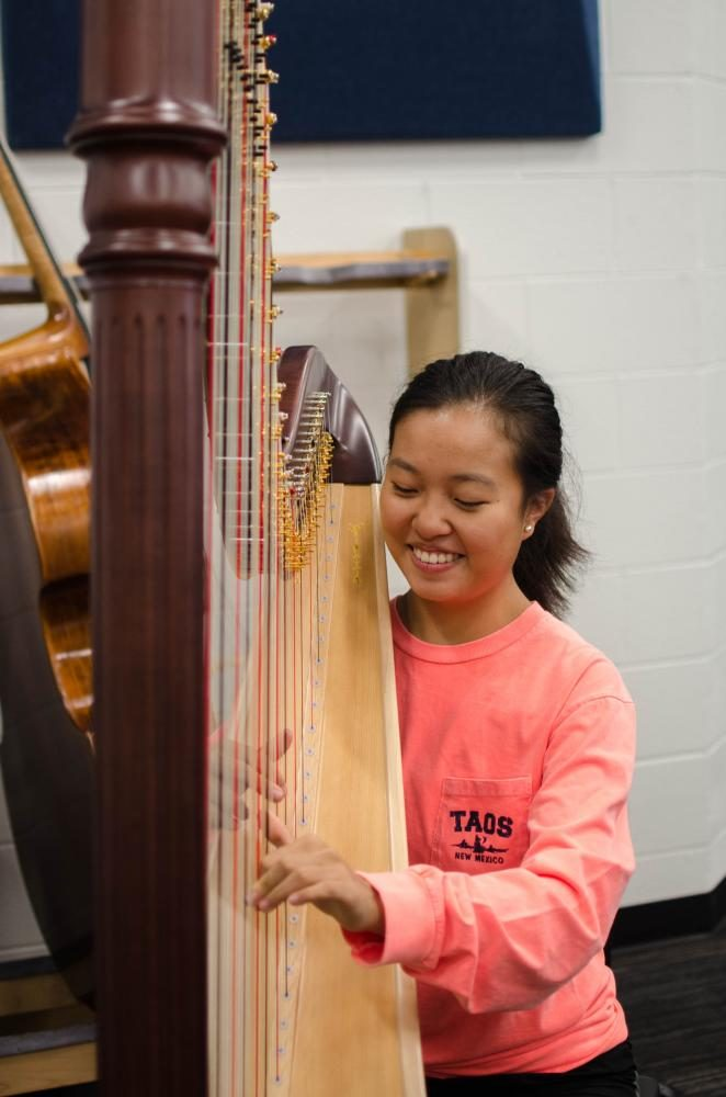 Sophomore Aleena Li practices on the brand new harp in the orchestra room.