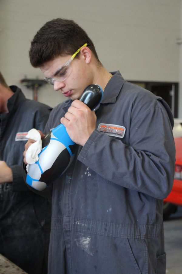 Hudnall, an Auto Collision student at OATC, wipes down his painted bowling pin with a rag.