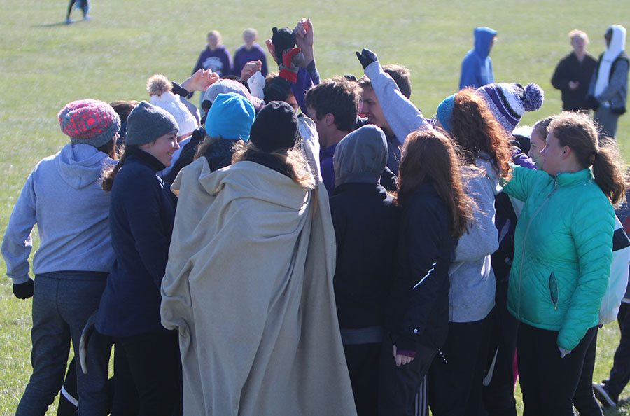Fellow runners on the cross country team huddle up in effort to hype up Eric Gawlick before his race at Rim Rock on Oct 28.