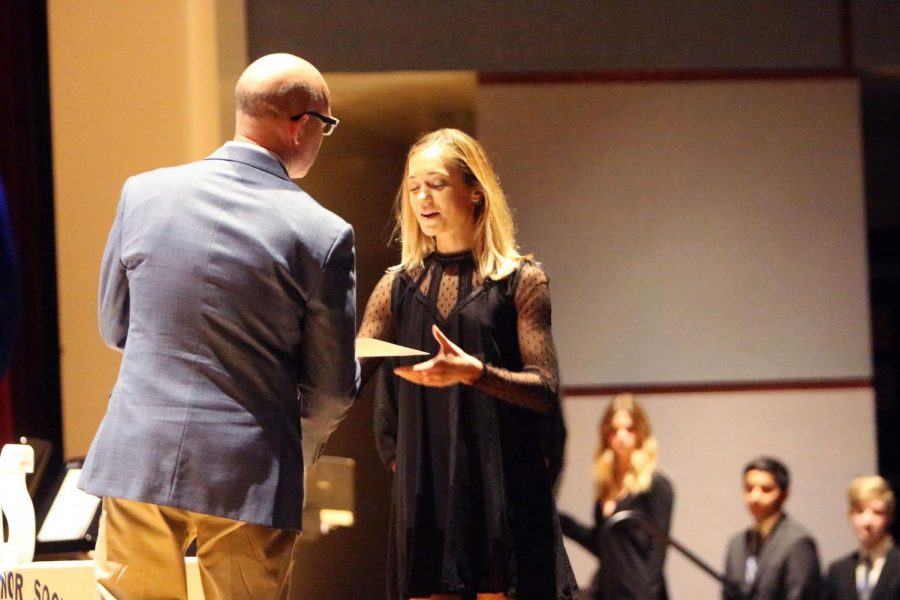 Junior Gracie Lyle shakes Mr. Petereson's hand as she accepts her letter of induction Nov. 14 in the PAC.