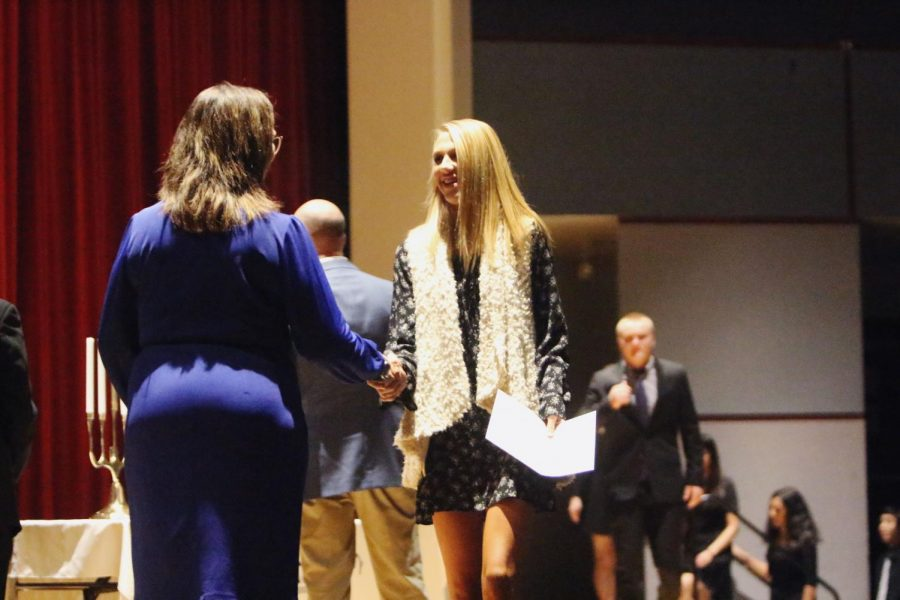 Senior Avarie Howard accepts her certificate of induction Nov. 14 in the PAC.