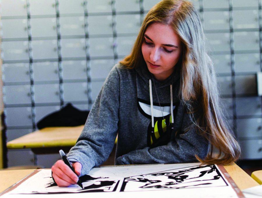 Senior Gabby Gillespie works on an ink piece for her portfolio class.