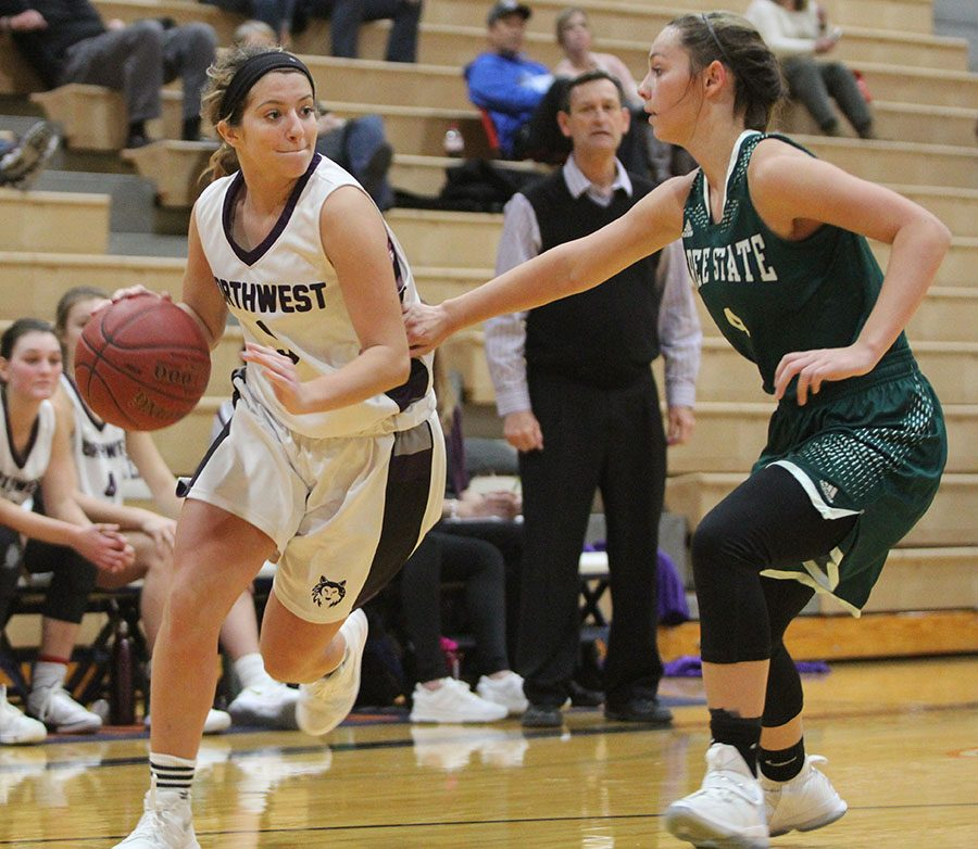 Senior guard Bridget Harrison dribbles the ball baseline during the second half of the Huskies matchup with the Firebirds. Harrison scored in double-figures for the third consecutive game, with 10 points Thursday.