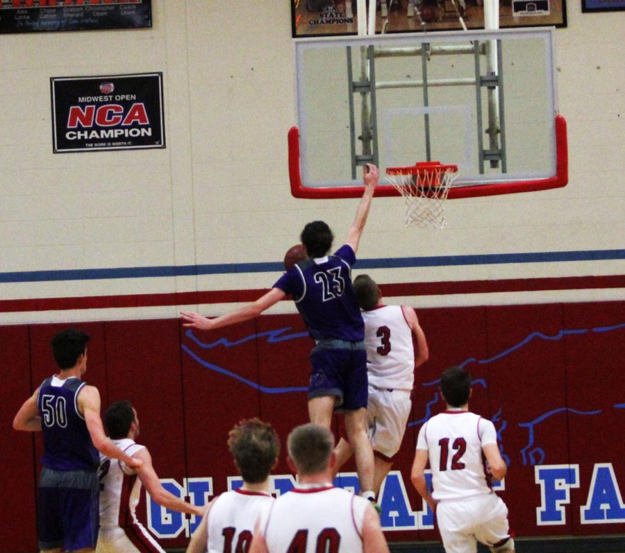 During the first half of the Huskies game against Ozark High, senior forward Parker Braun (23) leaps for a rejection.