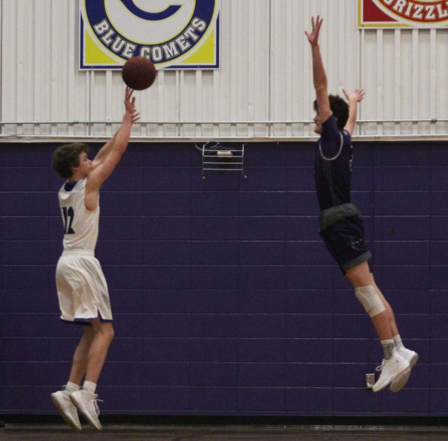 Blue Valley Northwest freshman guard Jack Chapman (3, pictured right) leaps to attempt to alter a 3-point attempt for the Ravens during the second half of the Huskies matchup with the Ravens at Pittsburg High Jan. 19. The Huskies defeated the Ravens, 52-38.