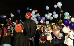 A crowd of people release balloons to honor John Albers.