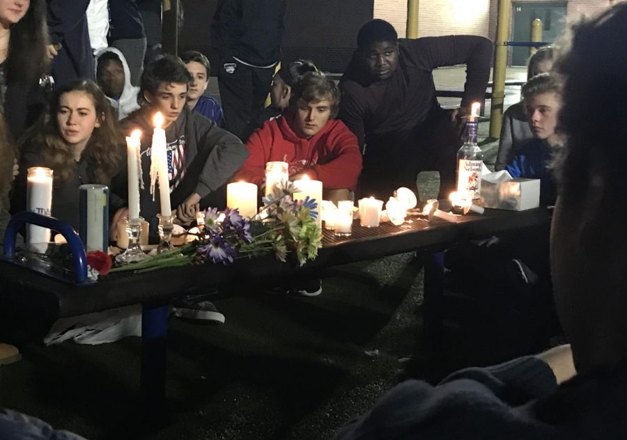 People circle around a bench holding candles and flowers in silence.