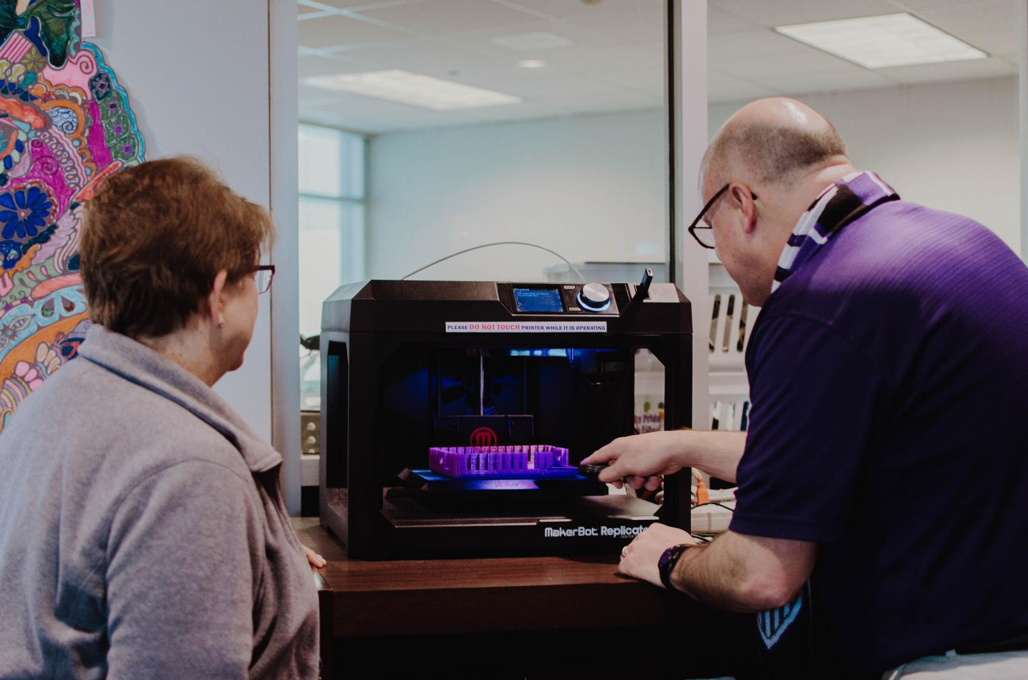 Librarians Mary McCabe and Craig Odle work on fixing the MakerBot.