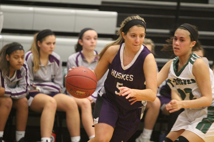 Blue Valley Northwest senior guard Bridget Harrison (5) dribbles past a defender during the second half of the Huskies matchup with Blue Valley Southwest at BVSW Feb. 2. The Huskies defeated the Timberwolves, 59-46.