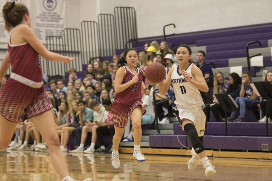 Blue Valley Northwest junior guard Haley Shin (11) dribbles the ball in transition during the first quarter of the Huskies matchup with St. James Academy at BVNW Feb. 23. The Huskies were defeated by the Thunder, 37-33.