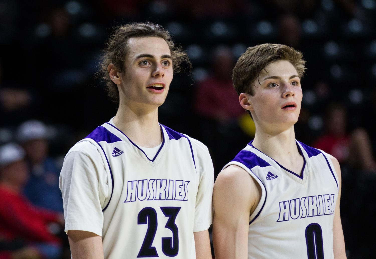 Senior forward Parker Braun (23) and junior guard Christian Braun (0) watch the action from the bench after checking out in the fourth quarter of the Huskies matchup against Lawrence High at Charles Koch Arena March 8. The Huskies defeated the Lions, 65-37.