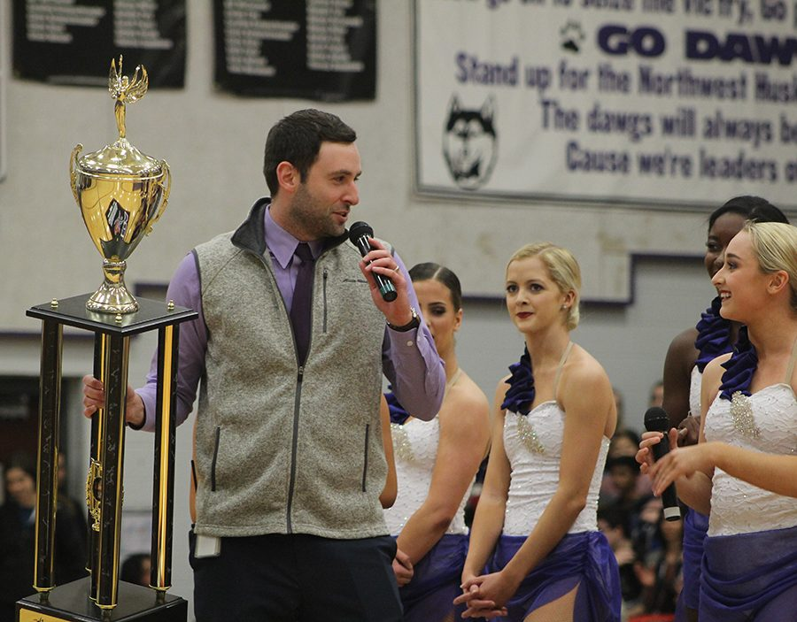 Associate principal Tyler Alexander is presented with the championship trophy by the Dazzlers at todays assembly.