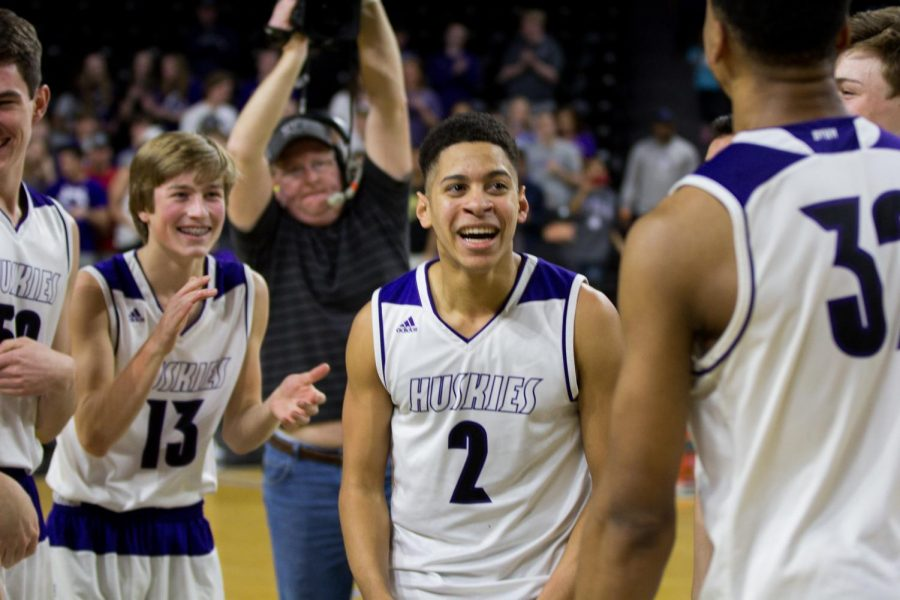 Blue Valley Northwest senior guard Max Johnson (2) smiles at senior forward Joe Pleasant (32) after the Huskies win over Lawrence Free State.