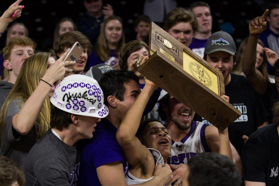 Blue Valley Northwest senior guard Max Johnson (2) holds the trophy in the air after the Huskies matchup with Lawrence Free State March 10 at Charles Koch Arena. The Huskies defeated the Firebirds, 51-40.