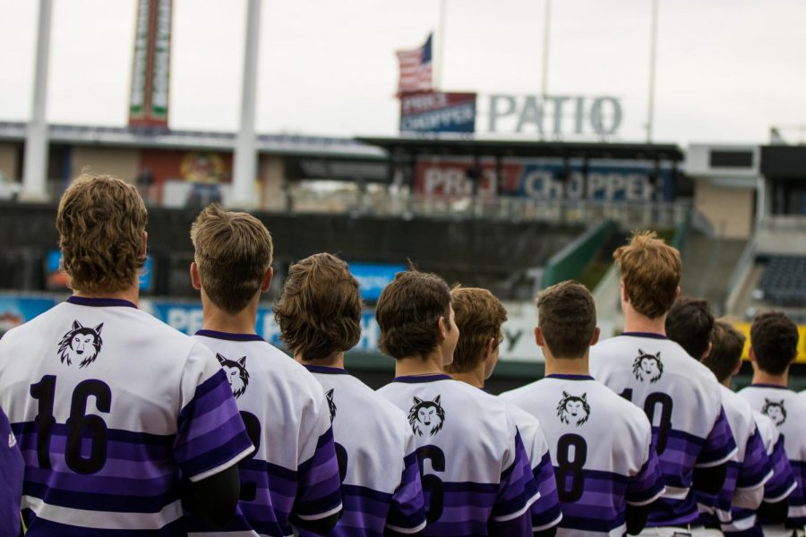 Blue Valley Northwest players line up during the National Anthem prior to the Huskies matchup with Summit Christian Academy at Kauffman Stadium April 21. The Huskies defeated the Eagles, 6-2.