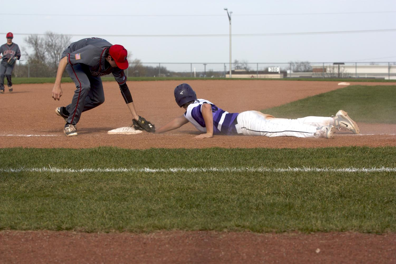 Senior Holden Missey dives back into third base after a Jaguars pickoff attempt in the Huskies matchup with Blue Valley West at the DAC April 24. The Huskies defeated the Jaguars, 10-3.