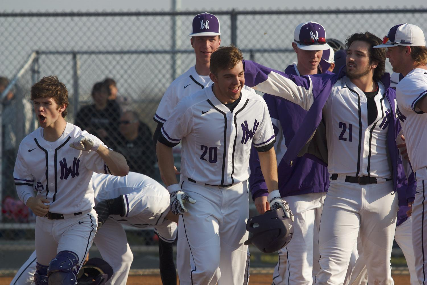 Members of the Huskies team celebrate junior Sean Roseborough's (20) third inning home run during the Huskies matchup with Blue Valley at BVHS April 10. The Huskies defeated the Tigers, 15-10.