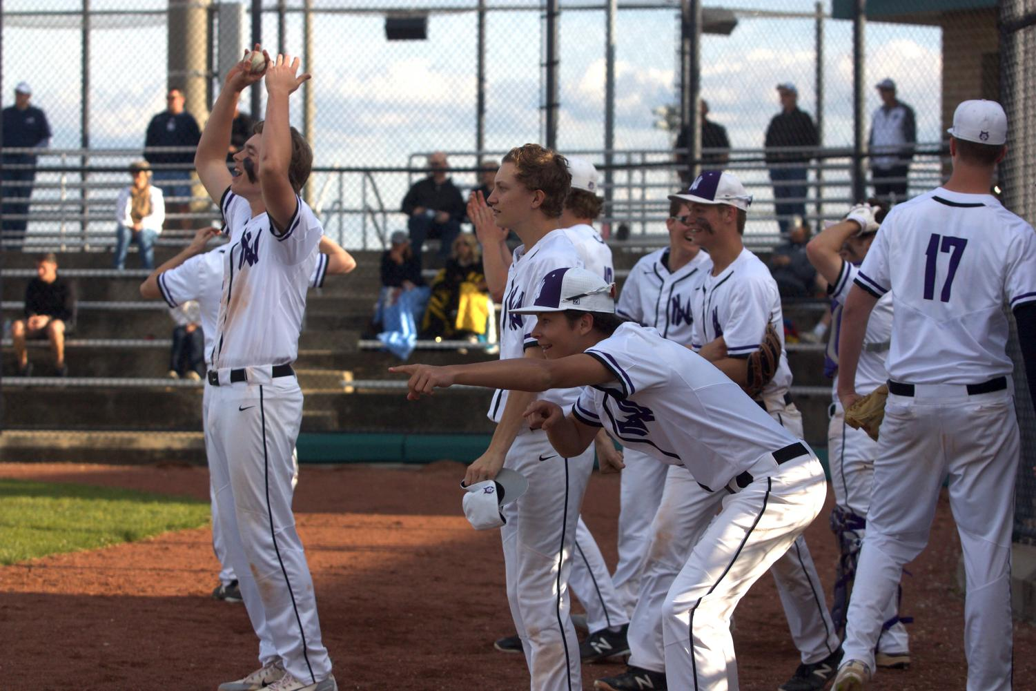 Members of the team celebrate after an RBI double by junior Sean Roseborough. The Huskies defeated the Mustangs, 12-3.