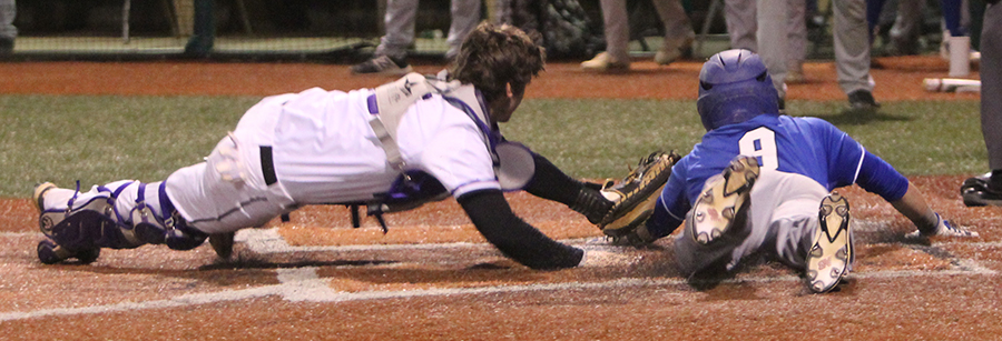 Senior catcher Clayton Leathers tags out a Rogers High School runner at home plate at Lawrence Free State April 19. The Huskies lost to the Mounties, 7-4.