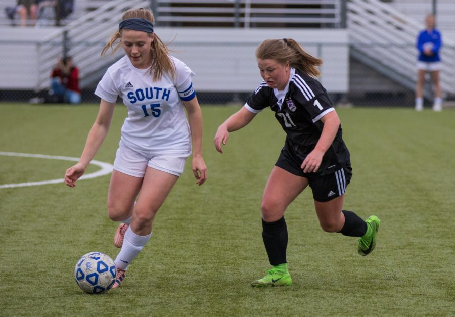 Junior Sydney Reeder (21) defends an Olathe South player during the Huskies matchup with the Falcons Friday April 20. The Huskies lost to the Falcons, 3-2.