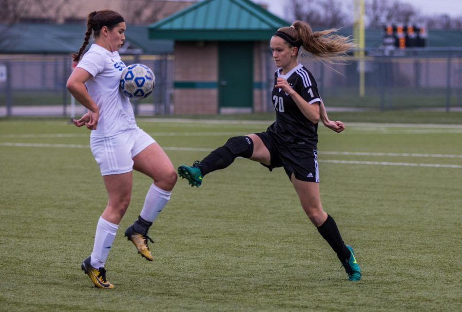 Senior Gabrielle Nabors (20) follows through after kicking the ball during the Huskies matchup with Olathe South. The Huskies lost to the Falcons, 3-2.
