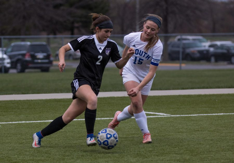 Senior Lily Reid (2) takes on a defender during the Huskies matchup with Olathe South. The Huskies lost to the Falcons, 3-2.