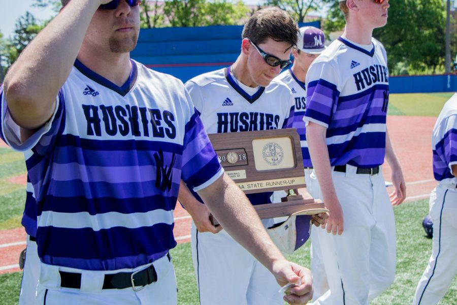Senior Scott Duensing and the Huskies walk off the field with the runner-up trophy after the Huskies matchup with Blue Valley at Hoglund Ballpark May 26. The Tigers defeated the Huskies, 1-0.