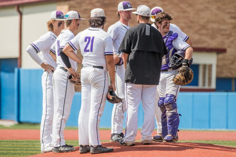 Head coach Corby Lange visits senior Will Dennis and the rest of his infield during a mound visit in the top of the first inning of the Huskies matchup with Washburn Rural at Hoglund Ballpark May 24. The Huskies defeated the Blues, 9-3.