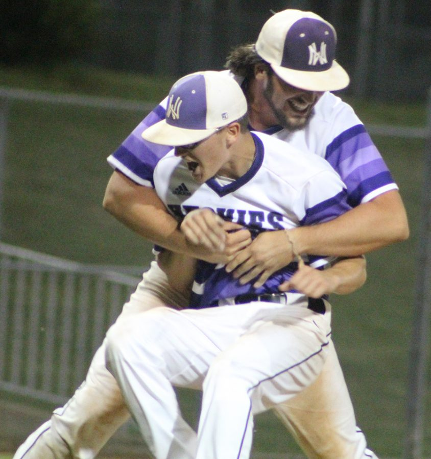 Senior third baseman Josh Fiene hugs senior pitcher Scott Duensing after their game against Olathe East High School at the DAC. The Huskies defeated the Hawks 2-0.