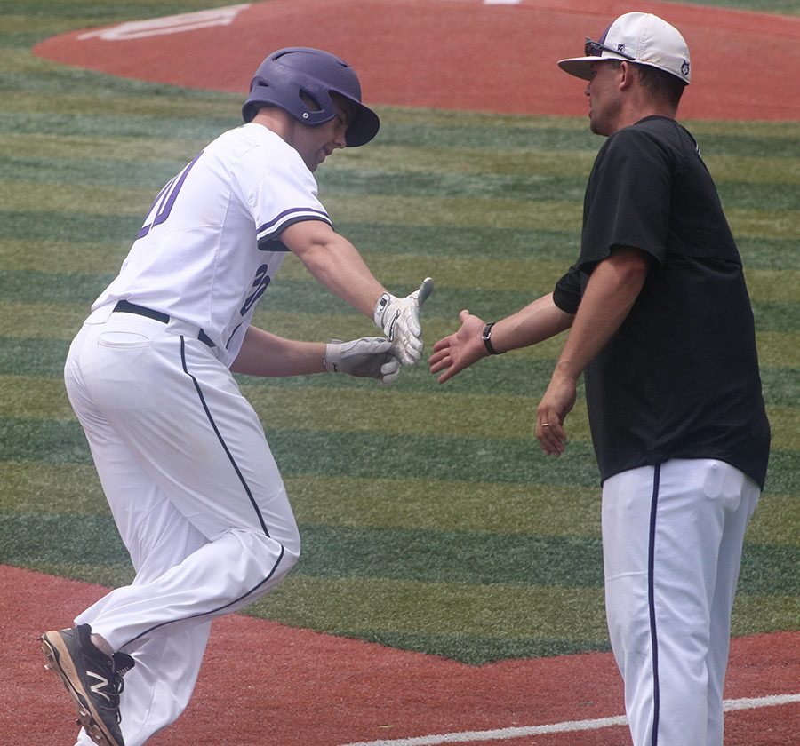 Head coach Corby Lange high fives junior Sean Roseborough after hitting a home run against Washburn Rural at Hoglund Ballpark May 24. The Huskies defeated the Blues 9-3.