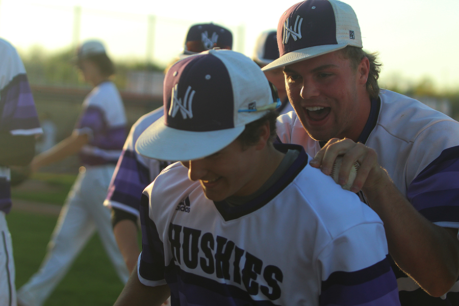 Senior pitcher Will Dennis congratulates junior left fielder Tyler McQuinn after throwing out a Blue Valley North runner at the DAC May 4. The Huskies defeated the Mustangs 5-1.