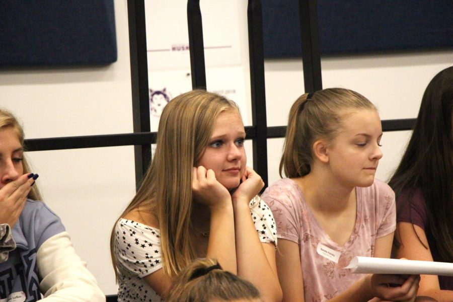 Freshmen Kimberly Gibson and Natalie Policky listen to a class instruction in Symphonic Choir.