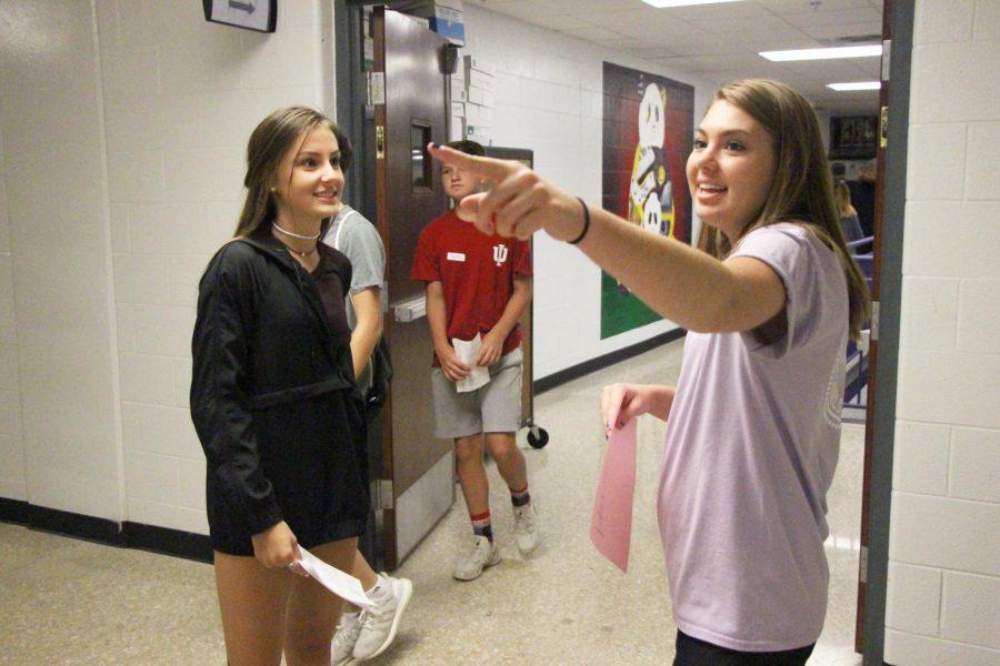 Senior Molly Rysko directs freshman Aly Hofmann to her class during freshman orientation.