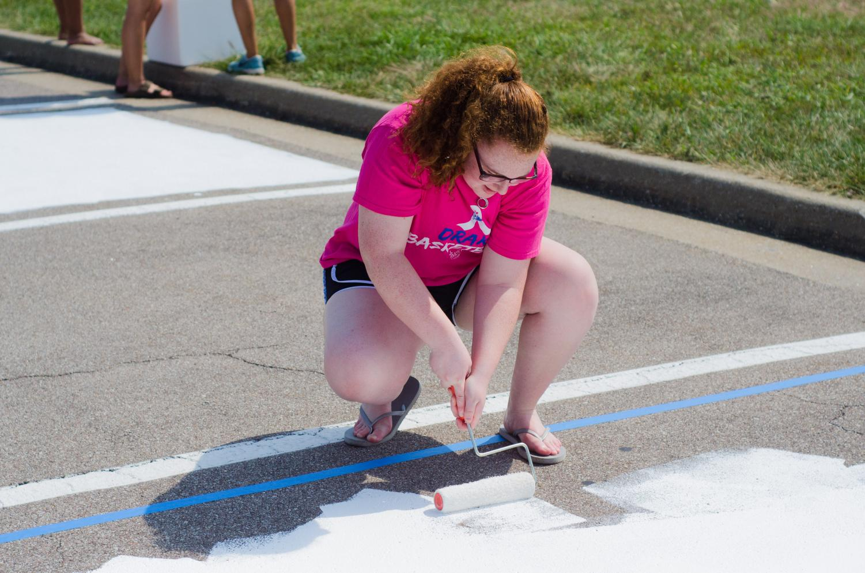 2018 graduate Robin DeWoskin paints her senior spot last year.