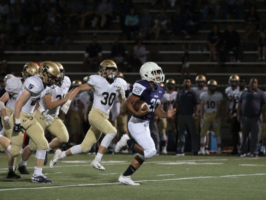 Junior+running+back+Avion+Tucker+%2826%29+runs+for+a+49+yard+touchdown+in+the+game+against+St.+Thomas+Aquinas+on+Thursday+Sept.+13+at+the+DAC.+The+Huskies+were+defeated+by+the+Saints%2C+49-14.