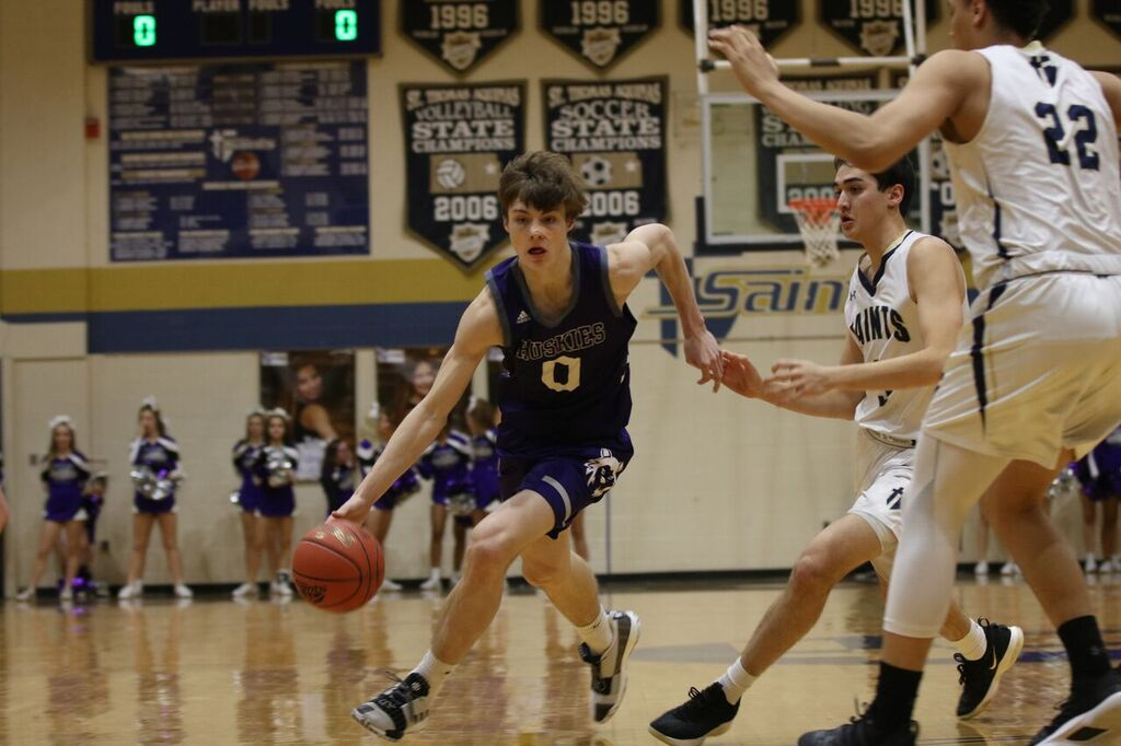Senior Christian Braun drives the ball in the game against Saint Thomas Aquinas on Friday Jan. 25 at STA. The Huskies defeated the Saints, 67-58.