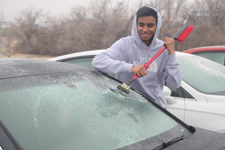 Senior Abhilash Arnipalli scraps ice off his car on Feb. 6 at BVNW.