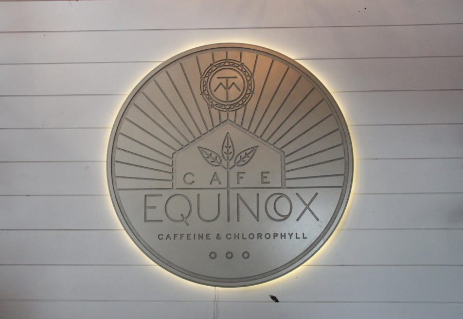 The cafe area offers many different seating areas, including one with a large, glowing Cafe Equinox sign.