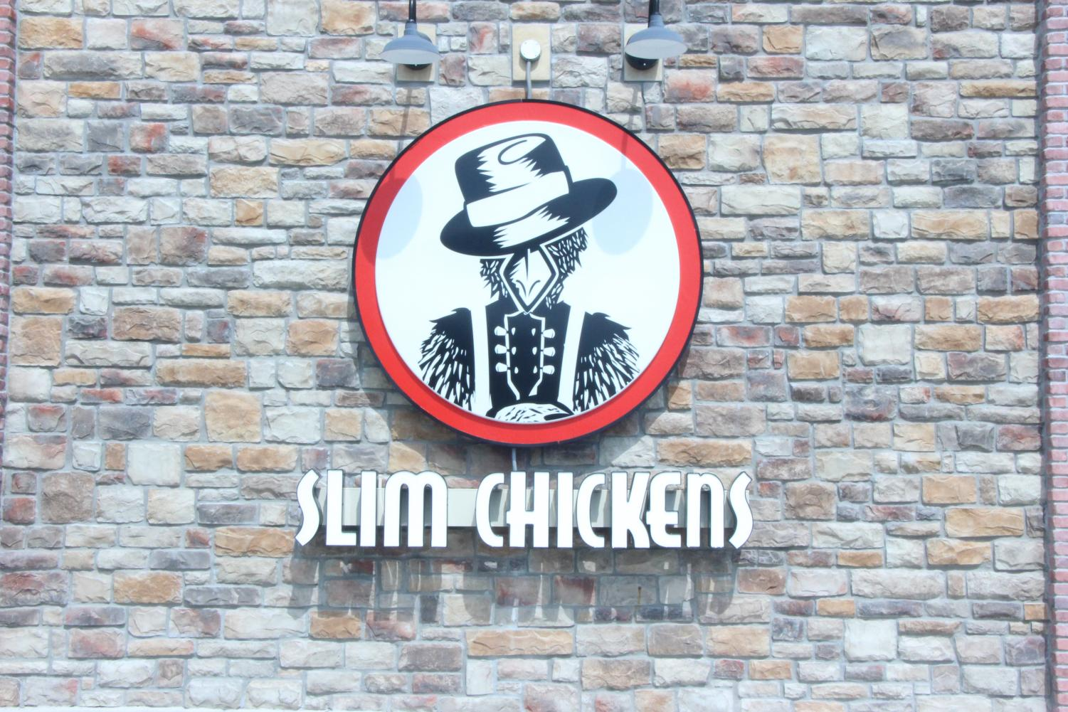 The red and white Slim Chickens logo is hung outside of the restaurant.