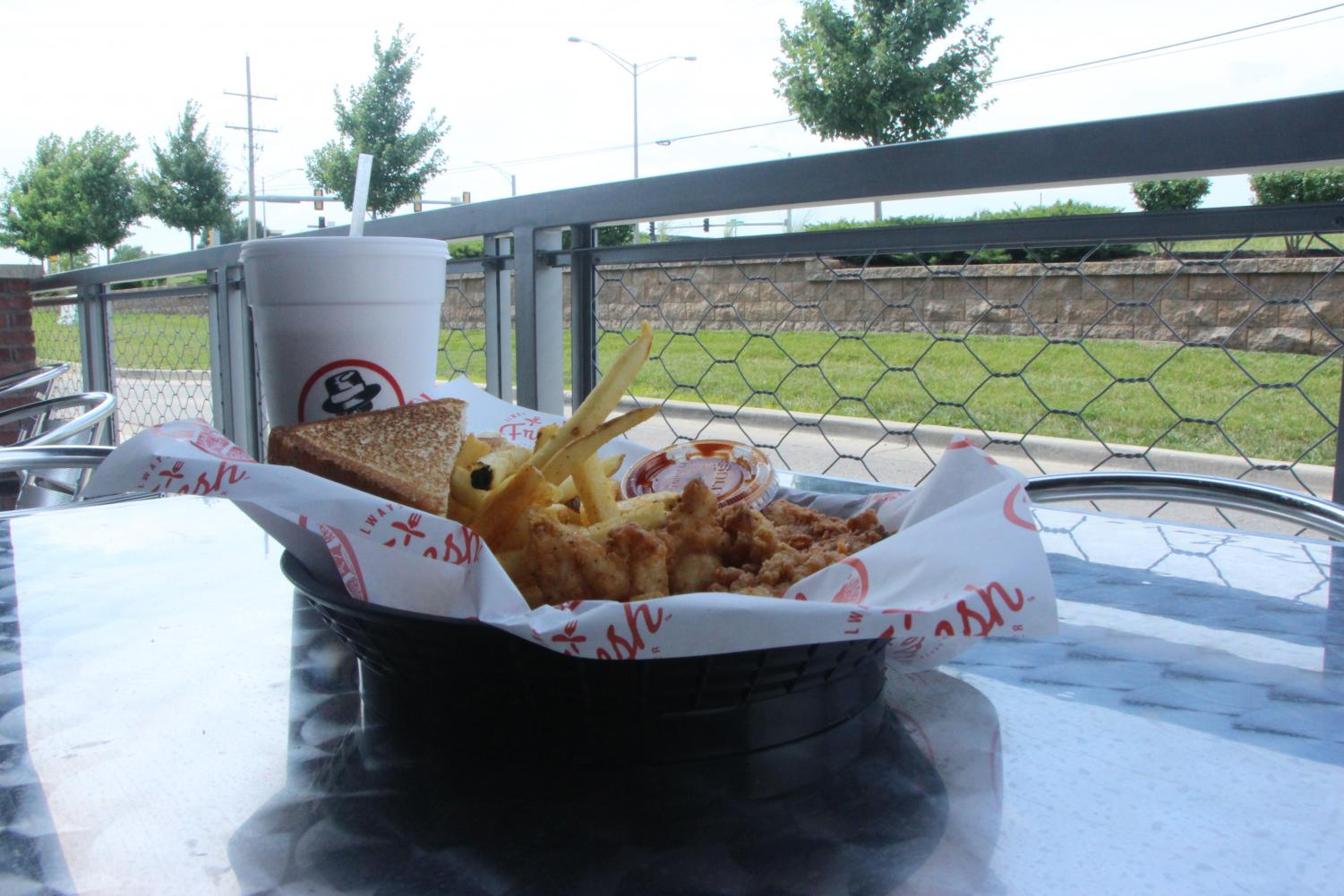 The three piece chicken tender meal from Slim Chickens sits on a table outside.