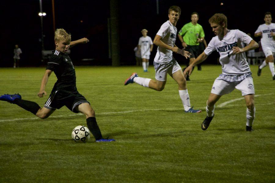 Junior Aidan Knauth kicks the soccer ball during the varsity soccer game, on Aug. 30.