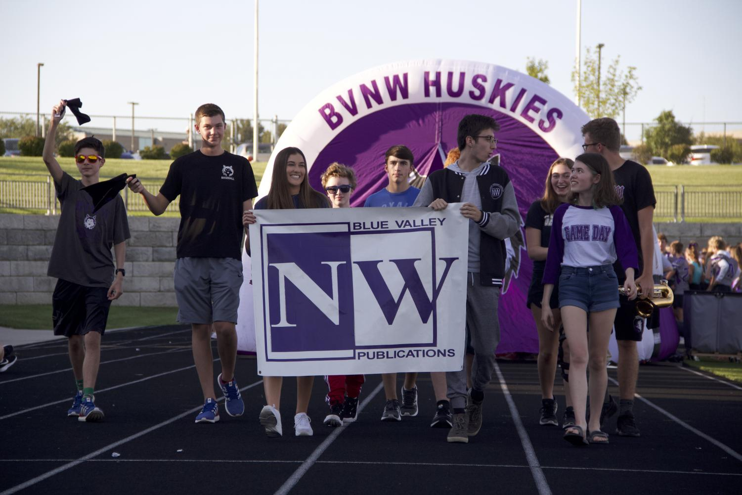 The+Husky+Headline+broadcast+staff+carries+their+poster+as+they+walk+across+the+track+on+Husky+Night.+