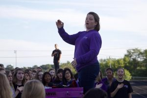 Choir director Beth Richey-Sullivan conducts the choir students during the National Anthem before the Husky Night parade in August of 2019.