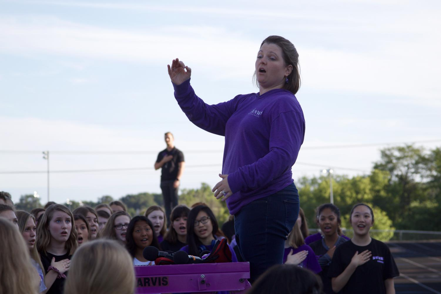 Choir+director+Beth+Richey-Sullivan+conducts+the+choir+students+during+the+National+Anthem+before+the+Husky+Night+parade.+