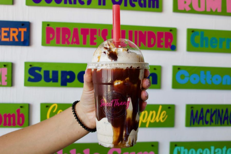 A Custom Milkshake with cappuccino chip ice cream, coffee, caramel and chocolate sauce is held in front of the flavor wall.